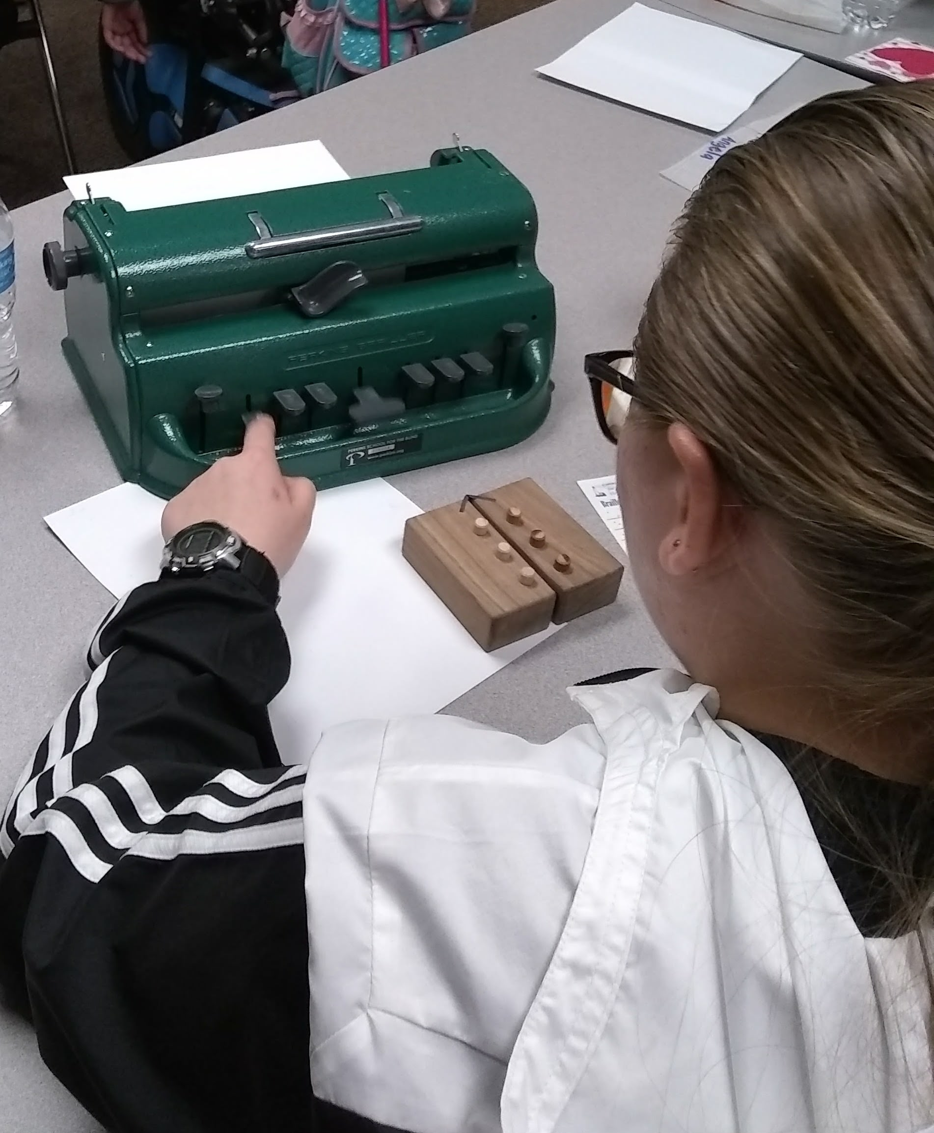 A student learns the braille cell using a swing cell and to write with a brailler.