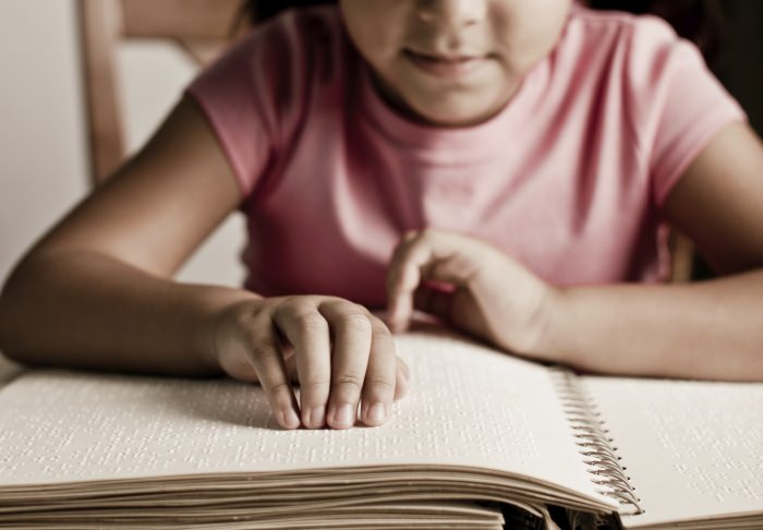 Image of girl reading braille