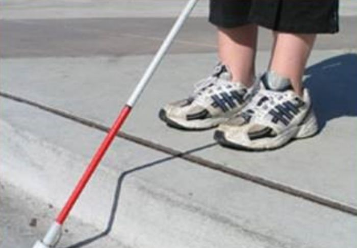 Photo of person standing at the edge of a curb with white cane